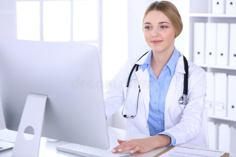 Young woman doctor at work in hospital looking at desktop pc monitor. Physician controls medication history records and. Exam results. Medicine and healthcare stock photos