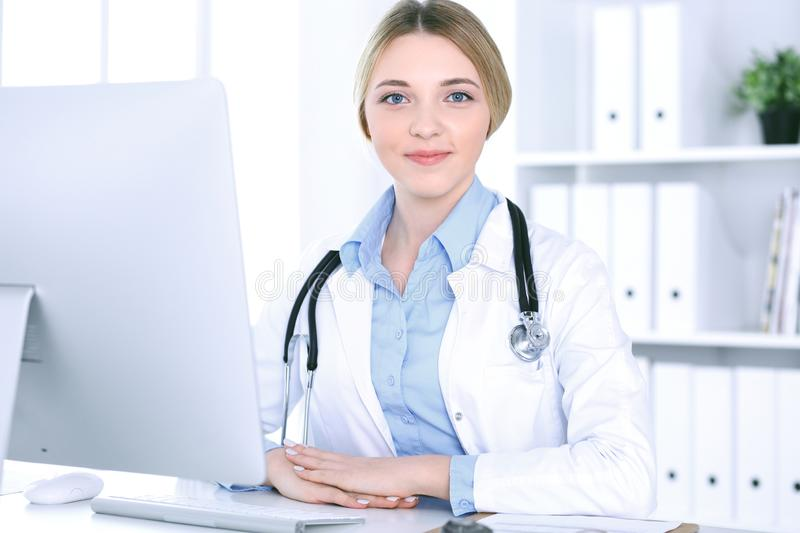 Young woman doctor at work in hospital looking at desktop pc monitor. Physician controls medication history records and. Exam results. Medicine and healthcare stock image