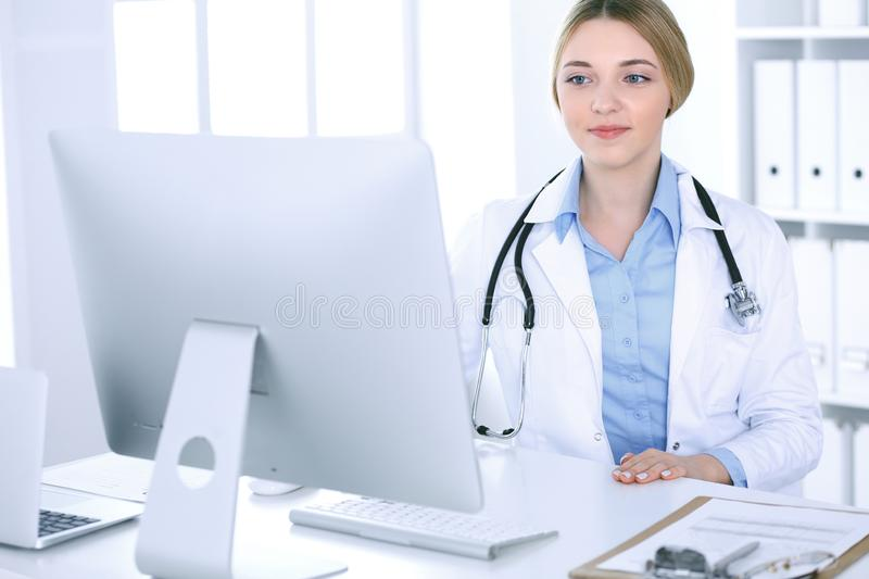 Young woman doctor at work in hospital looking at desktop pc monitor. Physician controls medication history records and. Exam results. Medicine and healthcare stock photo
