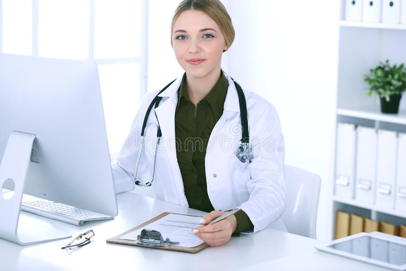Young woman doctor at work in hospital looking at desktop pc monitor. Physician controls medication history records and. Exam results. Medicine and healthcare stock images