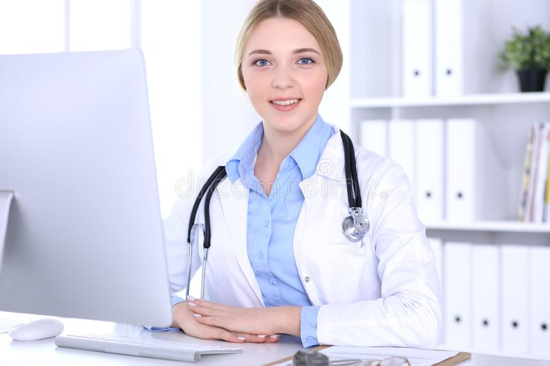 Young woman doctor at work in hospital looking at desktop pc monitor. Physician controls medication history records and. Exam results. Medicine and healthcare royalty free stock photos