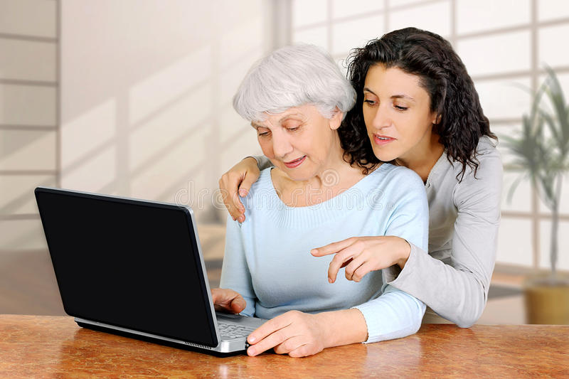 Young woman doctrine teaches daughter of an elderly woman laptop computer stock images