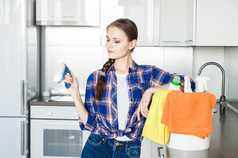 A young woman does the cleaning at home, washes the kitchen. Bucket with rags and yellow gloves on the table royalty free stock photos