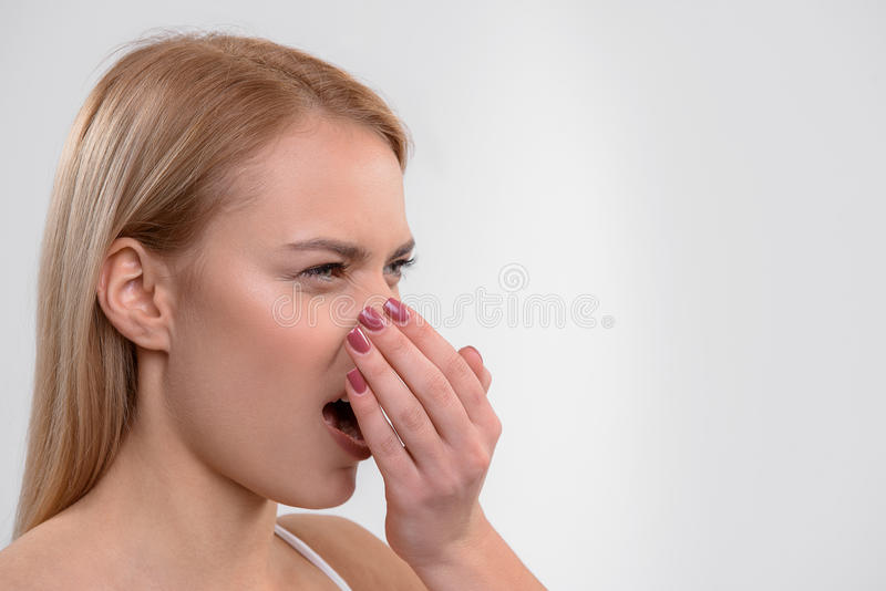 Young woman does not like her breath. Unpleasant smell from mouth. Dissatisfied girl is exhaling air from mouth on hand. Isolated and copy space in right side stock photo