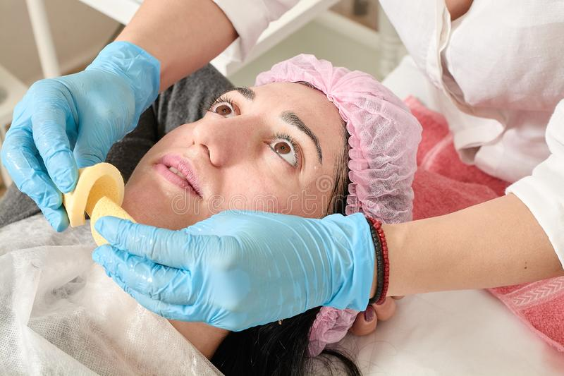 Young woman does professional facial massage in the beauty salon stock image