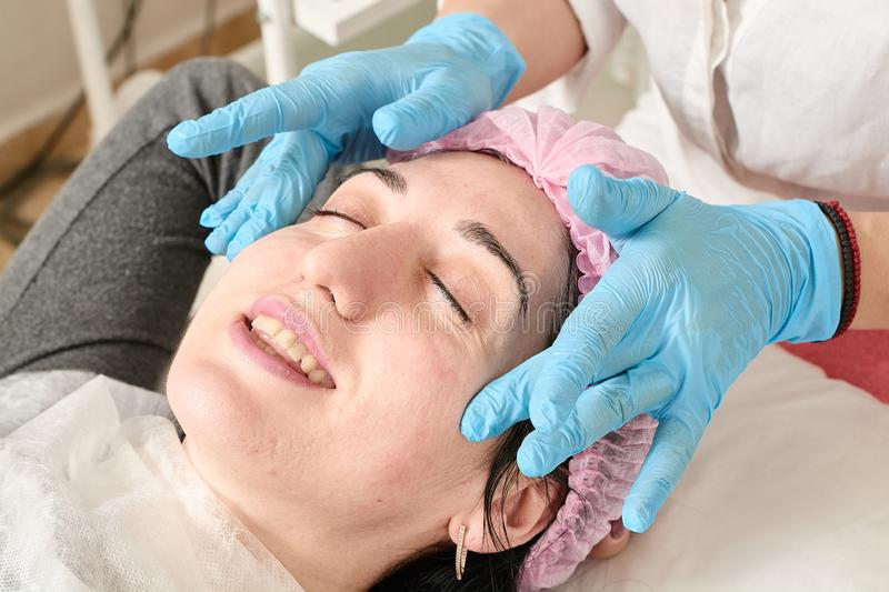 Young woman does professional facial massage in the beauty salon stock images
