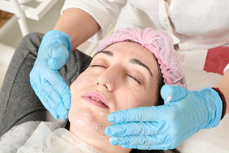 Young woman does professional facial massage in the beauty salon royalty free stock photo