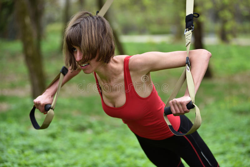 Young woman does suspension training with fitness straps in the stock photography