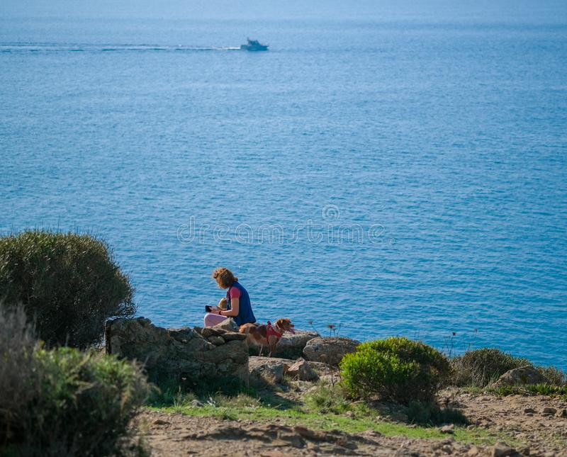 A young woman with a dog is resting while walking in the mountains. Along the sea. Tourist with pet on bright blue sea background. Walking routes, hiking trails royalty free stock image