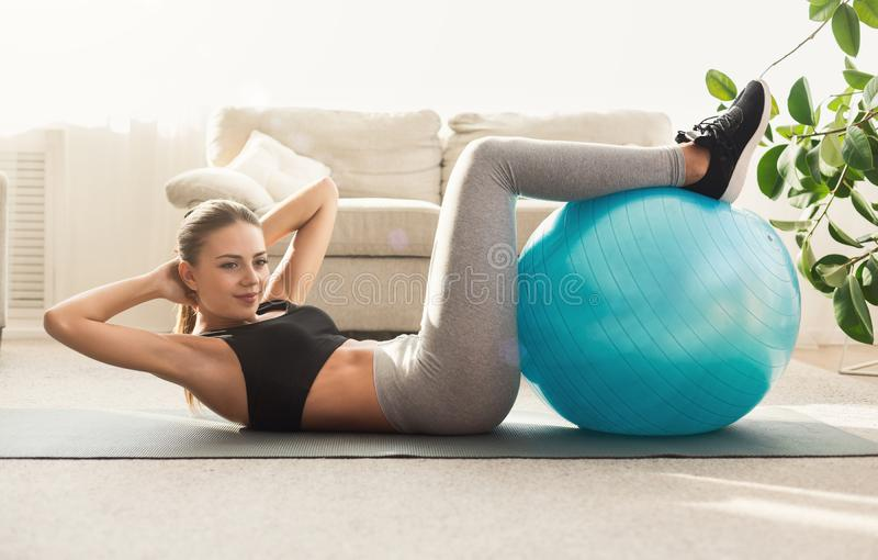 Young woman doing abs crunches with fitball. Lying on floor at home, copy space stock photos