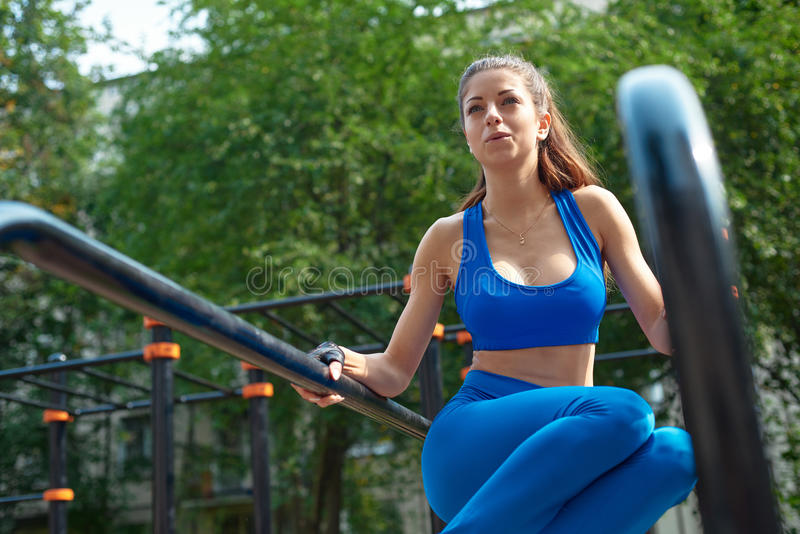 Young woman doing abs exercises outside on bars royalty free stock photos
