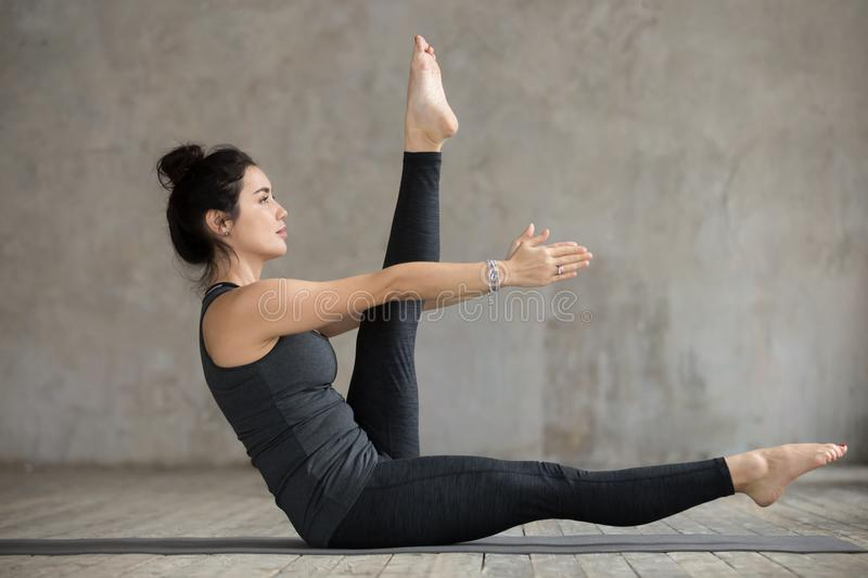 Young woman doing alternate leg stretch exercise. Young sporty woman practicing, doing alternate leg stretch exercise, working out, wearing sportswear, black royalty free stock image