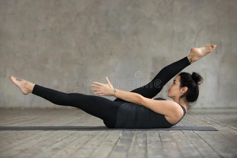 Young woman doing alternate leg stretch exercise. Young sporty woman practicing fitness, doing alternate leg stretch exercise, warm up pose, working out, wearing royalty free stock photography