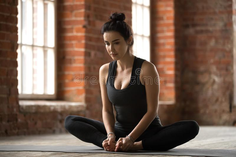 Young woman doing Butterfly exercise. Young sporty woman practicing yoga, doing Butterfly exercise, baddha konasana pose, working out, wearing sportswear, black stock photo