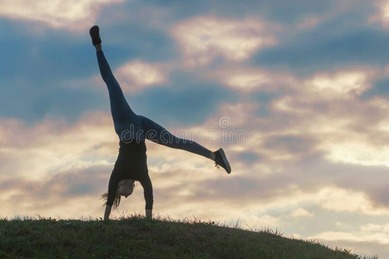 Young woman doing cartwheel on the grass Morning workout beautiful sunrise stock image