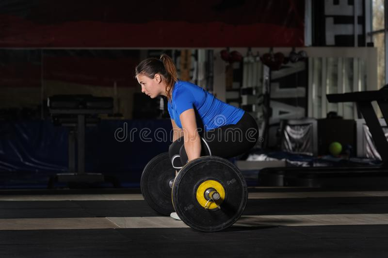 Young woman doing deadlift workout with heavy barbell in dark gym stock images