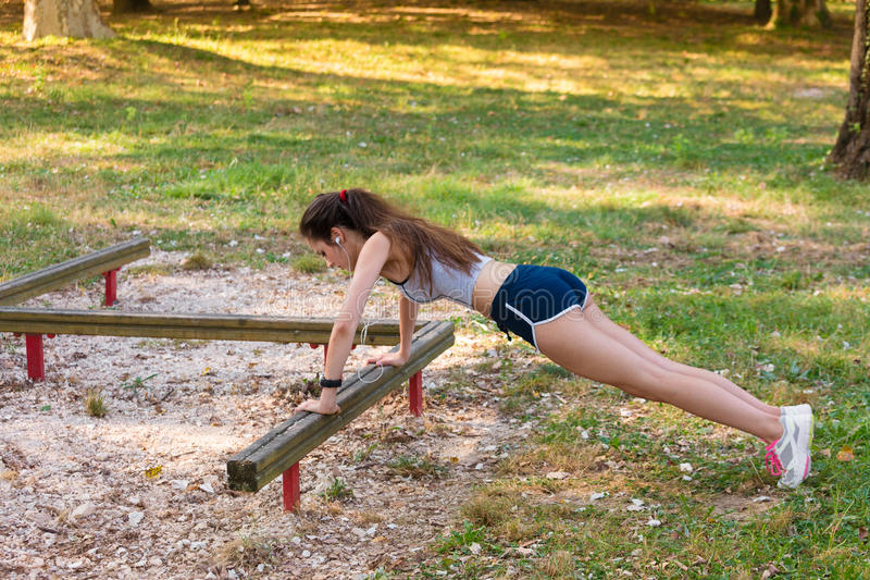Young woman doing doing push-ups. Portrait of Beautiful Young woman doing doing push-ups in the City park stock photography