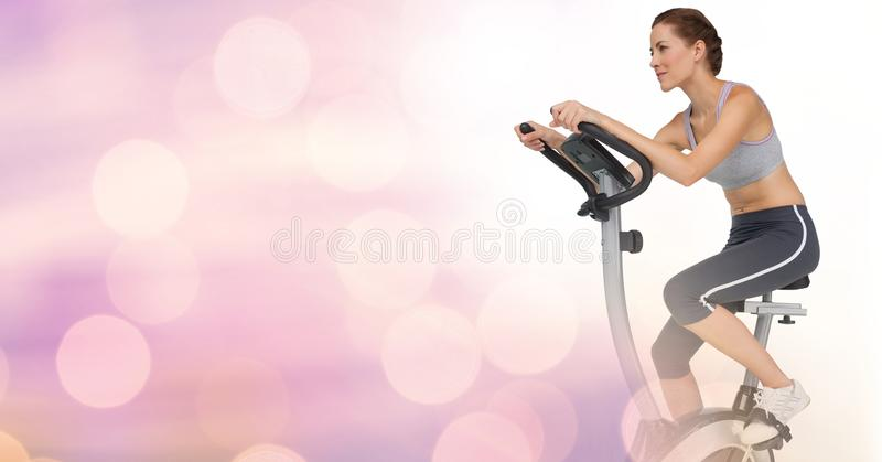 Young woman doing exercise bike with pink background stock images