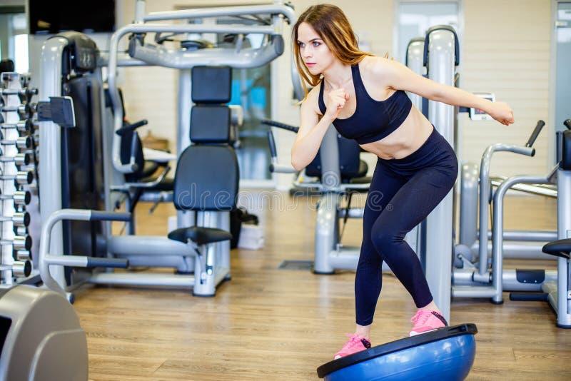 Young woman doing exercise on bosu ball. stock photography