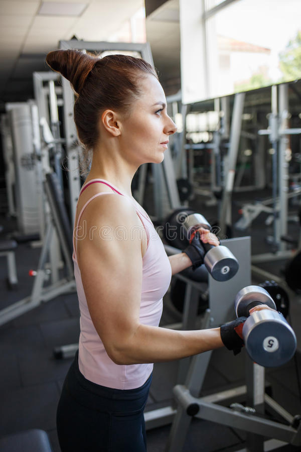 Young woman doing exercise in fitness center. Young confident woman doing biceps curl exercise with dumbbells in fitness center. Slim girl training in the gym stock image
