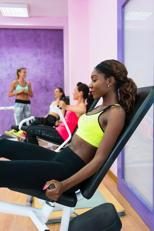 Young woman doing exercise for legs while attending group class. Happy young women with a healthy lifestyle doing exercise for toned legs while attending group royalty free stock image
