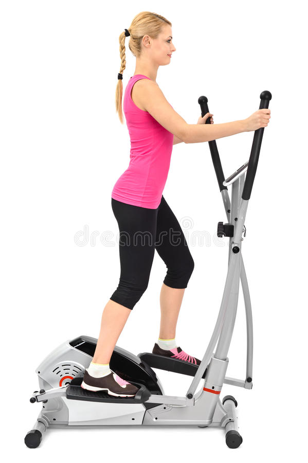 Young woman doing exercises on elliptical trainer royalty free stock images