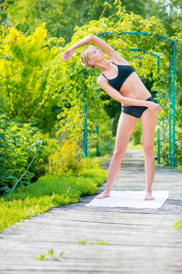 Young woman doing exercises in the park on a sunny day. Fitness stock images