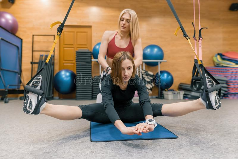 Young woman doing exercises with personal fitness instructor, exercises on the fitness loop system. Sport, athlete, training, royalty free stock photography