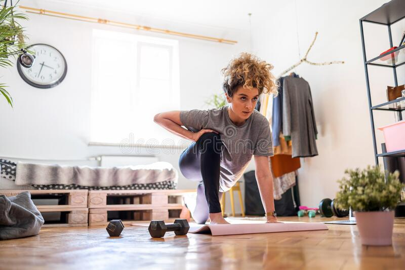Young woman doing fitness exercise at home royalty free stock photos
