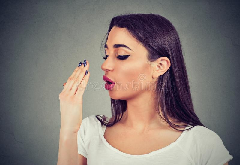 Young woman doing a hand breath test. Woman doing a hand breath test isolated on gray wall background stock photography