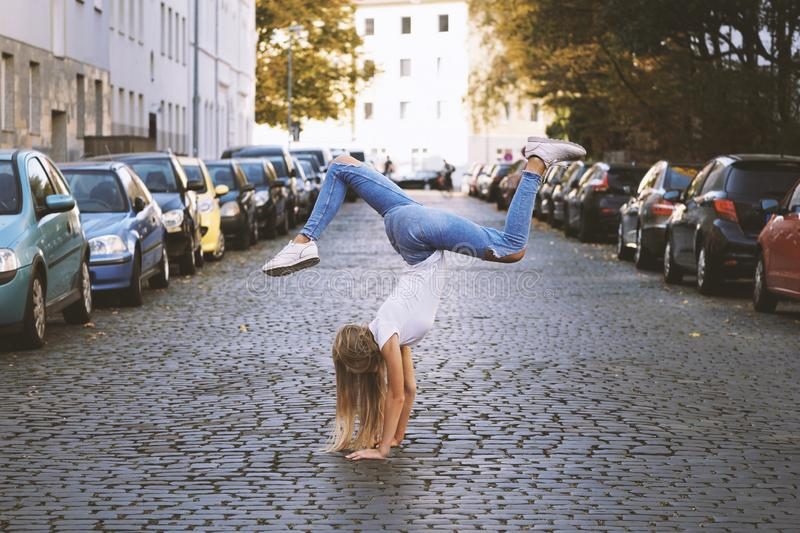 Young woman doing handstand on city street stock image