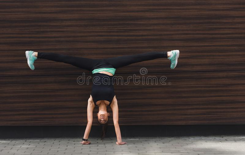 Young woman doing handstand on city street royalty free stock photography