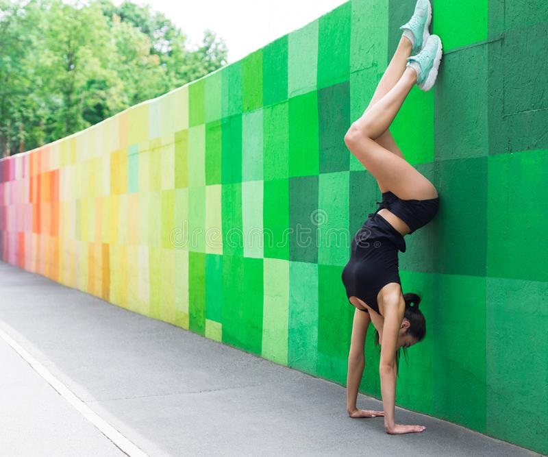 Young woman doing handstand on city street royalty free stock image