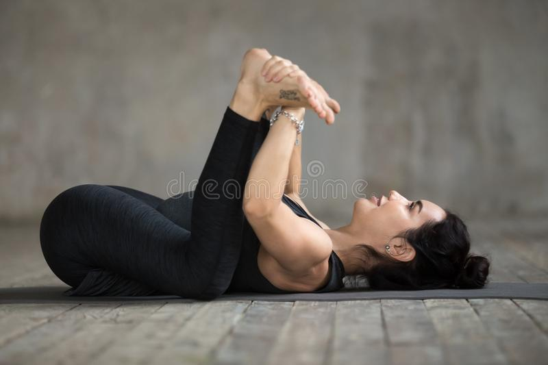 Young woman doing Happy Baby exercise royalty free stock photography