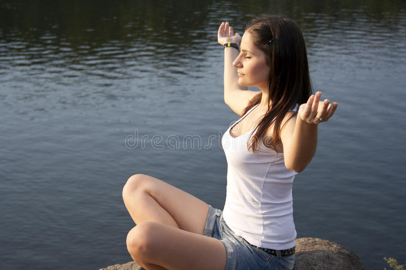 Young woman doing meditation outdoors stock photography