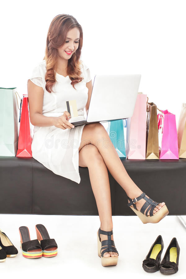 young woman doing online transaction and sitting between shopping bags and pair of shoes stock photos
