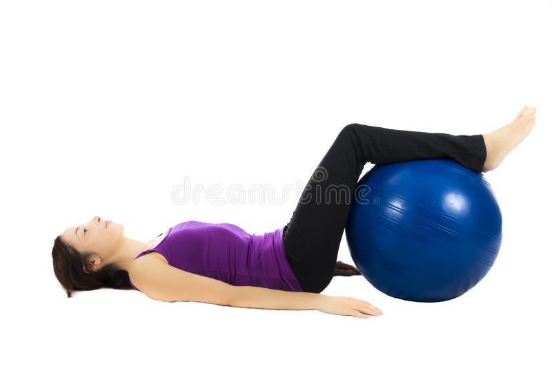 Young woman doing pilates ball exercises stock photo