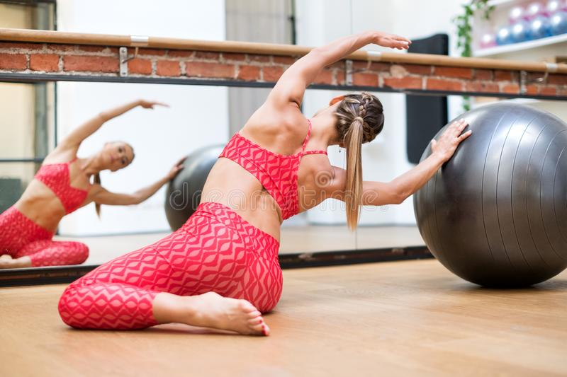 Young woman doing pilates mermaid exercises stock photography