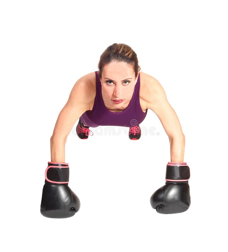 Young woman doing push up with boxing cloves stock photo