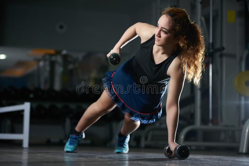 Young woman doing push-up exercise with dumbbell stock image