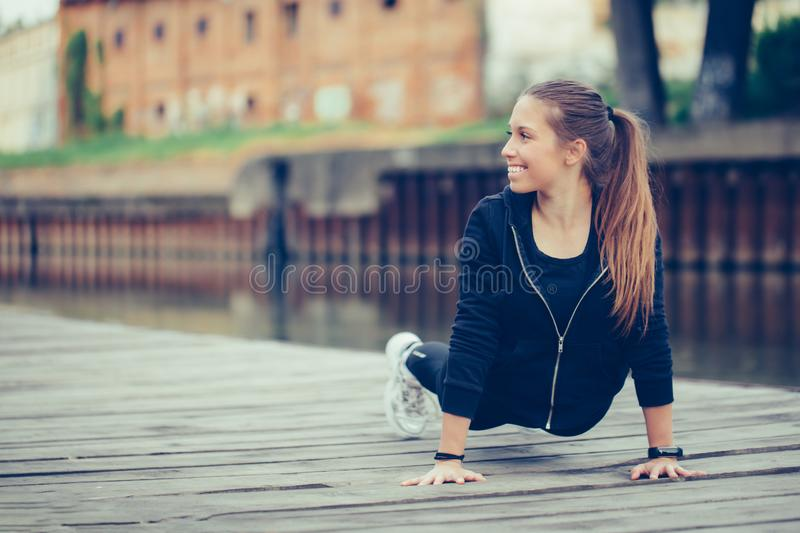 Young woman doing push up by the river. Young beautiful woman doing push up by the river. Attractive female runner taking break after jogging  by the river stock image