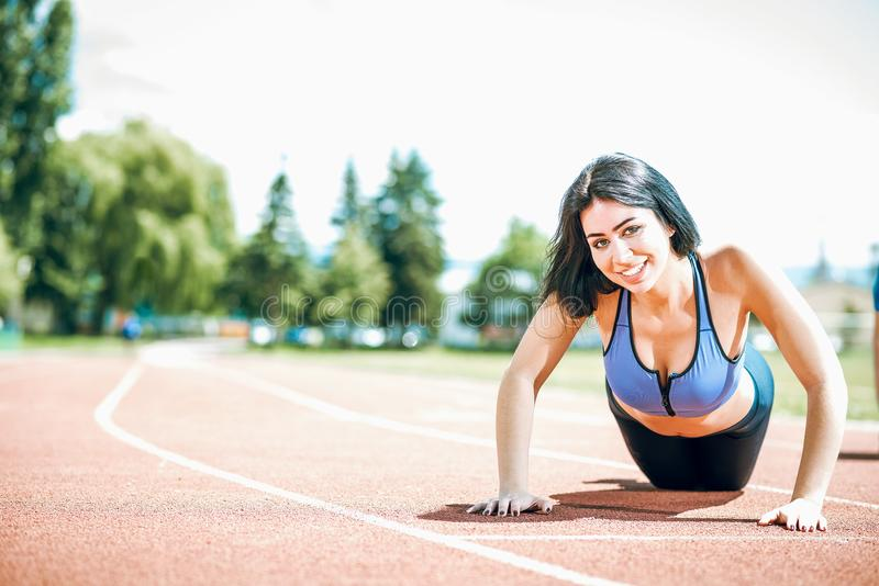 Young woman doing push ups on track field. Young woman doing push ups exercise outdoor on running track in park. Toned image stock photos
