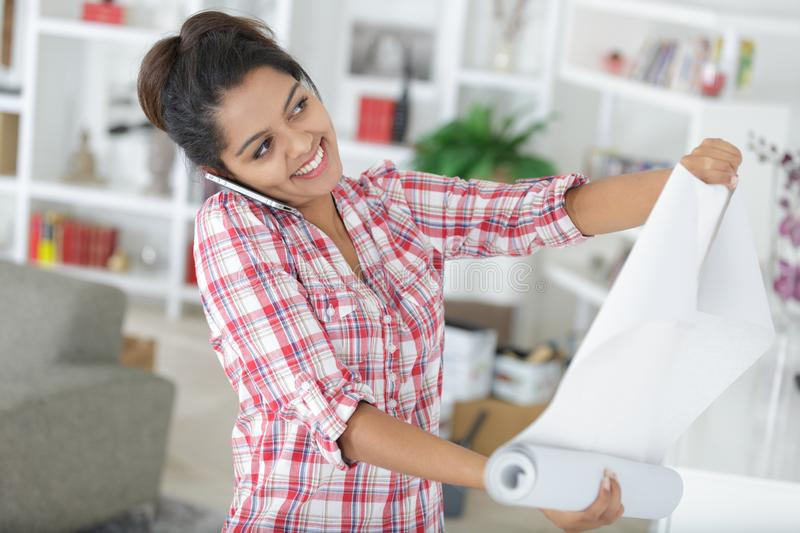 Young woman doing repairs in apartment wallpapering on wall. Woman royalty free stock photo