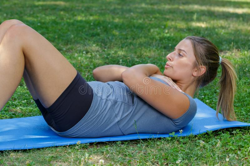 Young woman doing sit ups abdominal crunches royalty free stock image