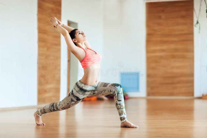 Young woman doing slimming exercise in the hall, yoga practice royalty free stock photo