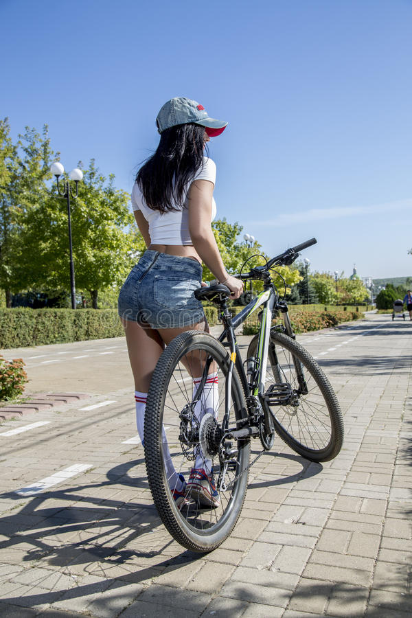 Young woman doing sports on the bike. royalty free stock photos