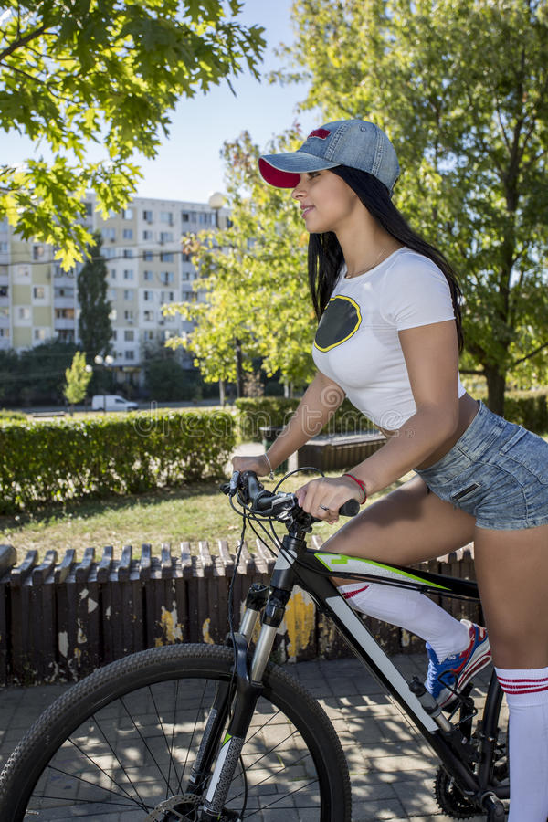 Young woman doing sports on the bike. royalty free stock image