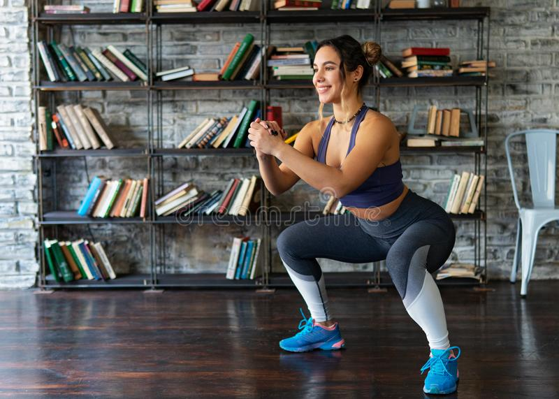 Woman doing squat workout and smiling during fitness training at home. Young woman doing squat workout and smiling during fitness training at home royalty free stock image