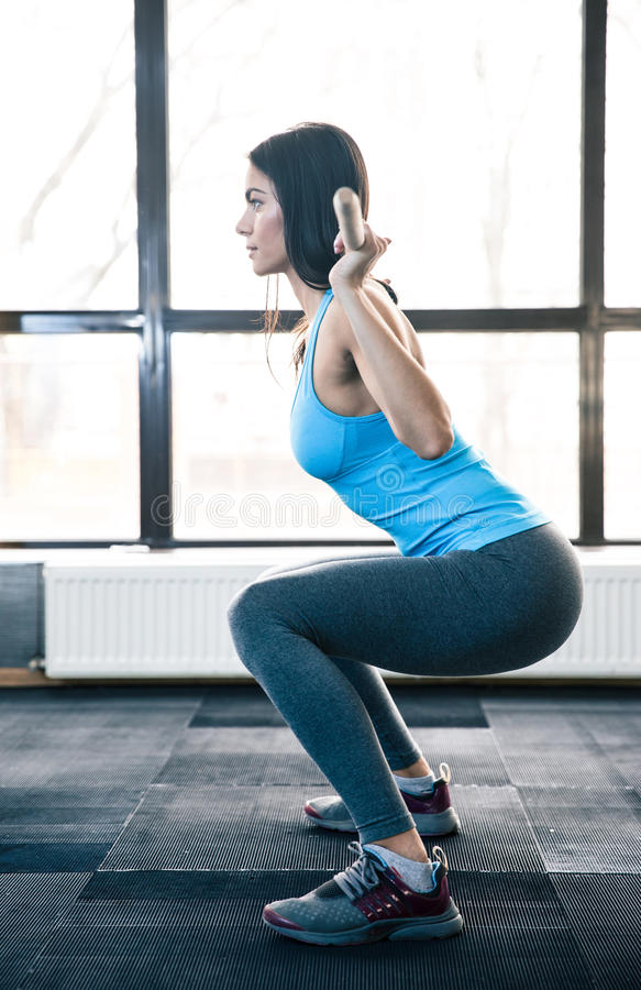 Young woman doing squats with barbell stock photos