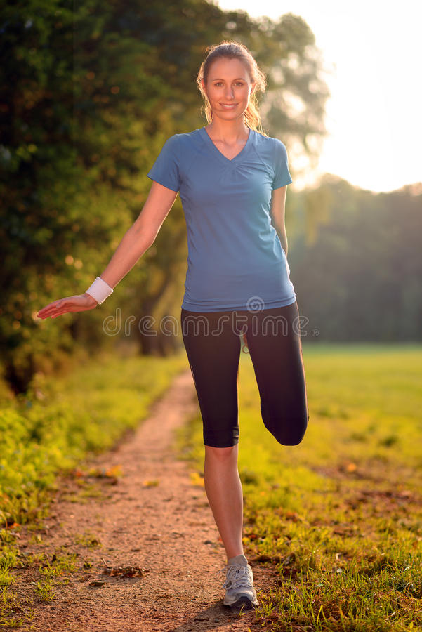 Young woman doing stretching exercises. As she limbers up her muscles to go on a jog or begin a workouts standing over a country track in golden light smiling stock photo